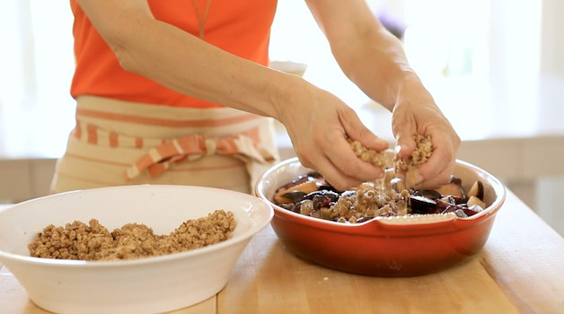 Adding crumb topping to a plum crumble