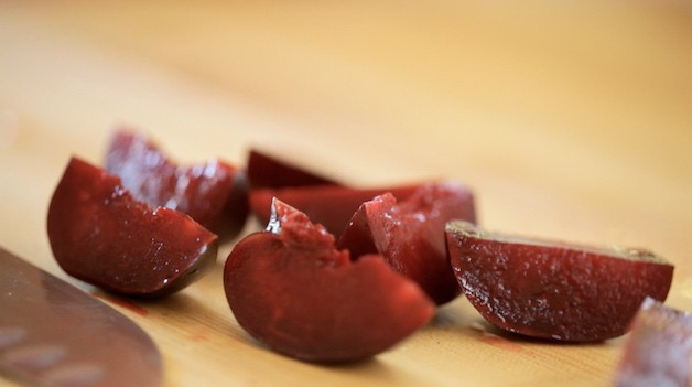 a red plum quartered on cutting board