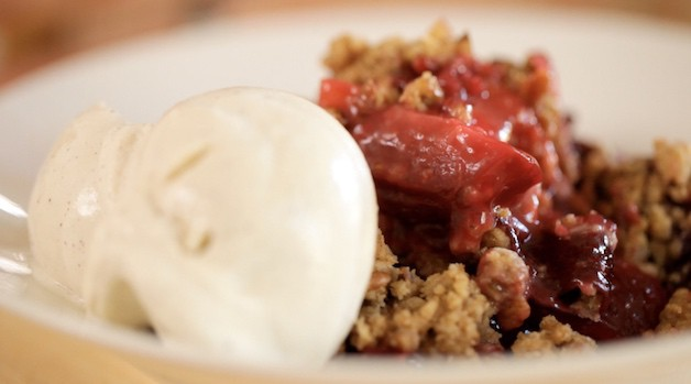 Plum Crumble in a shallow white bowl with vanilla ice cream