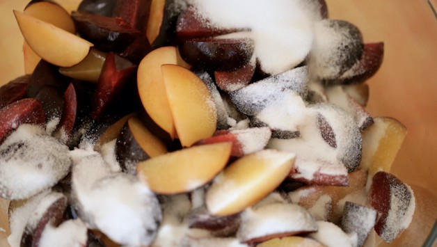 Tossing sliced Plums with sugar