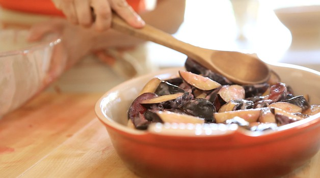 Patting plums down into a baking dish with a wooden spoon
