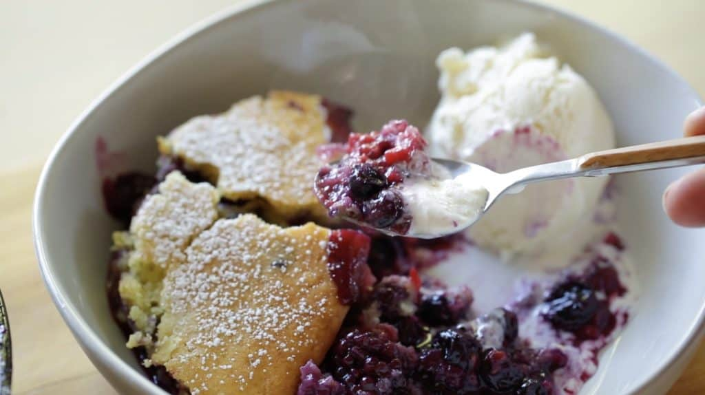 Ice cream melting on a Triple Berry Campfire Cake Recipe with a spoon taking a bite