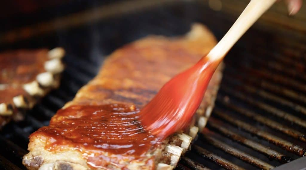 Applying homemade BBQ Sauce to a BBQ Ribs Recipe on the grill
