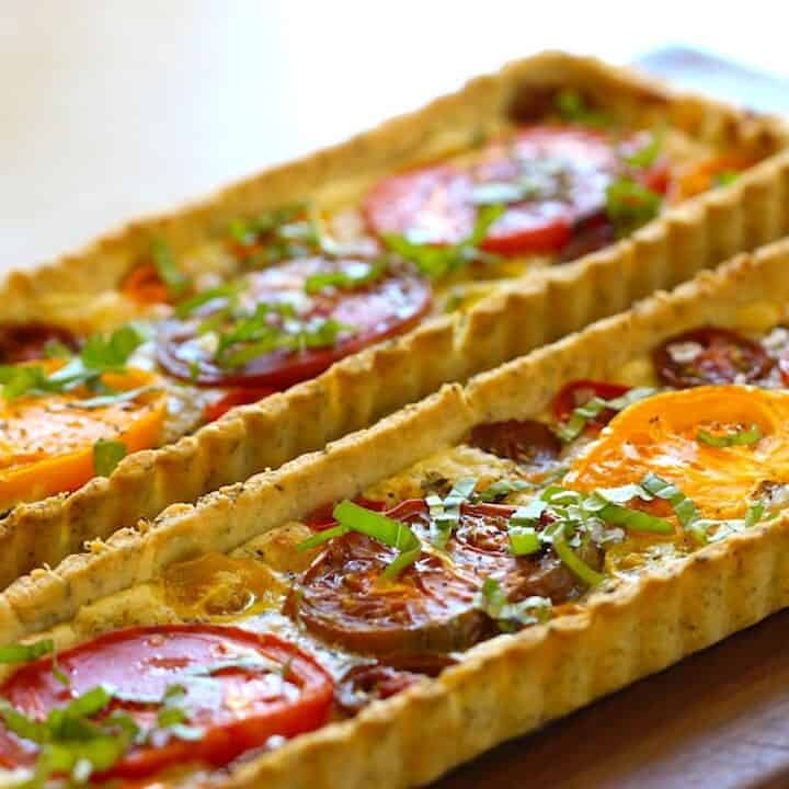 Two Tomato Tarts garnished with Fresh Basil on a Cutting Board