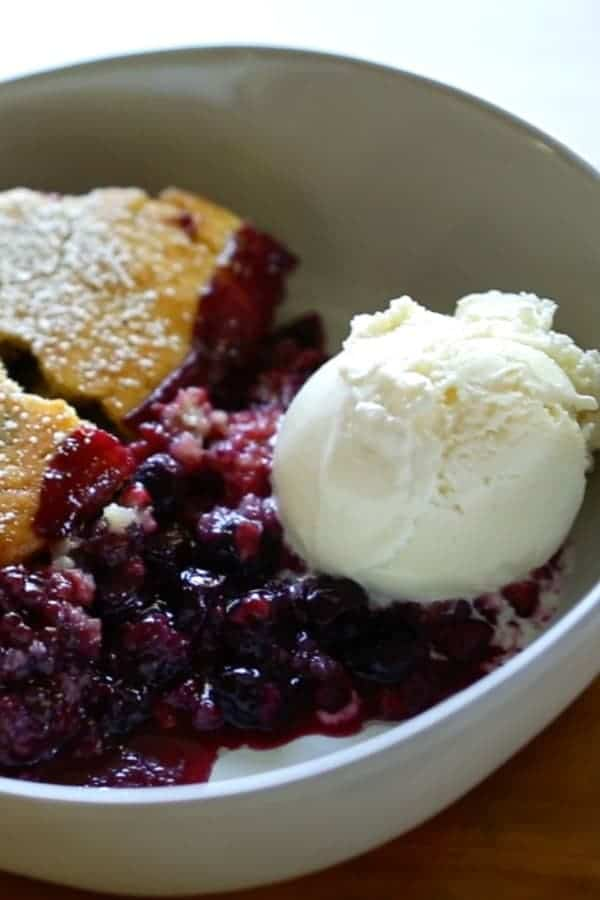 Triple Berry Campfire Cake Recipe in a cast-iron skillet with a serving portioned out in a bowl