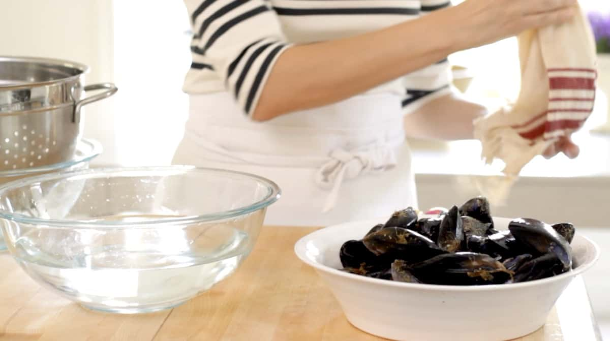 removing dish towel from a bowl of fresh mussels next to a bowl of fresh water