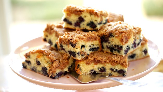 The Best Blueberry Crumb Cake Recipe cut into sqaures and piled high on a cake stand