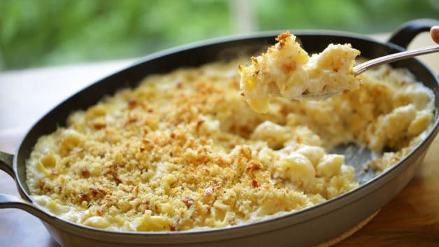 Large gratin pan full of baked mac and cheese with serving spoon showing a bite