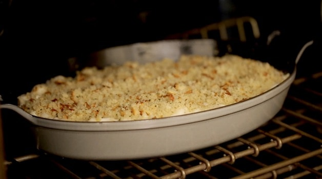 Mac and CHeese in a gratin pan placed in the oven to bake