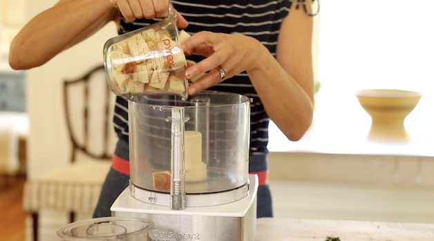 Placing bread cubes in food processor for homemade bread crumbs