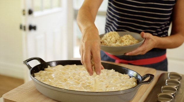 A person placing bread crumbs on top of mac and cheese in a gratin pan