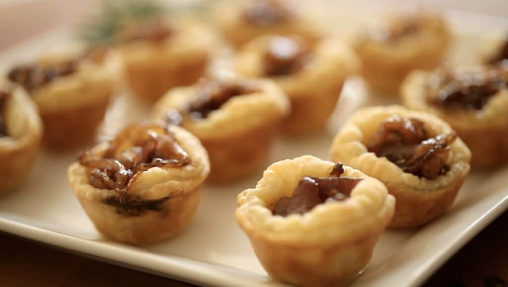 a collection of mini tarts made with puff pastry on a white platter