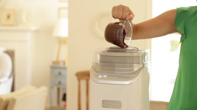 Melted chocolate being poured from a Pyrex pitcher into a running Ice Cream Machine