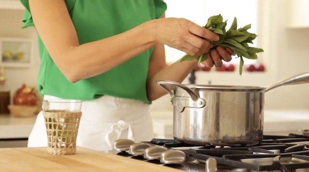 Adding fresh mint stems to a saucepot