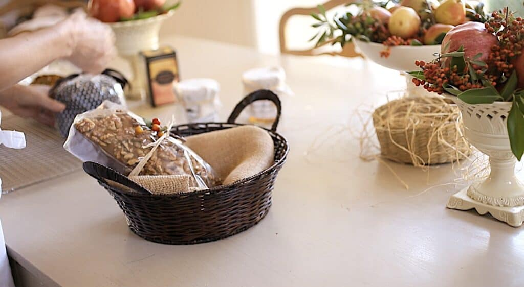 placing a packaged pumpkin bread into a basket lined with burlap