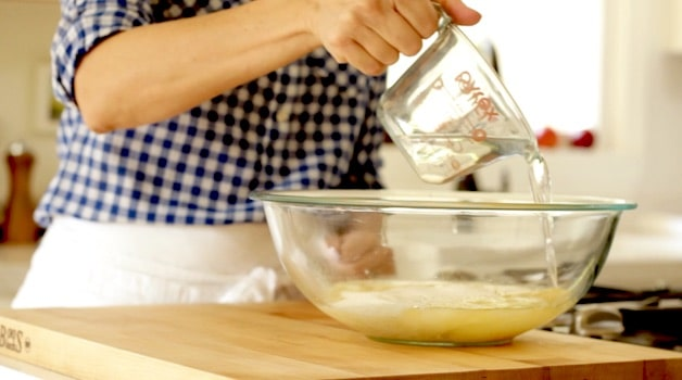 adding water to a bowl for a cake batter
