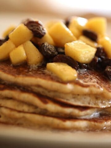 A stack of Apple Cider Pancakes with raisins and apples on top