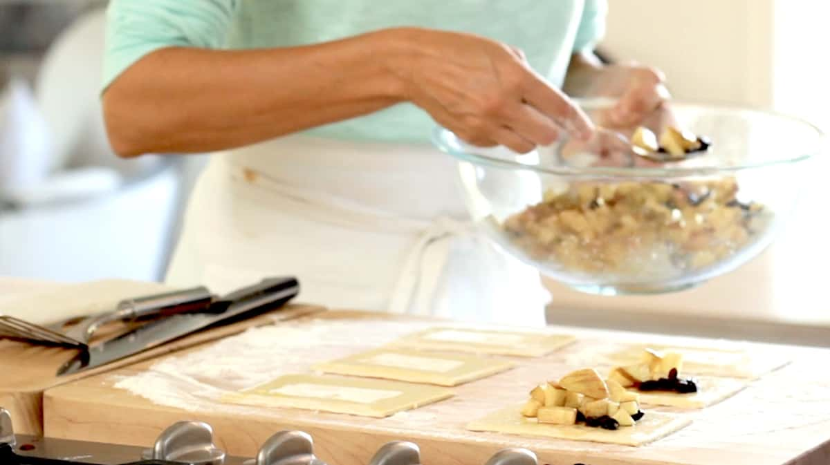 adding apple raisin mixture to pastry rectangles