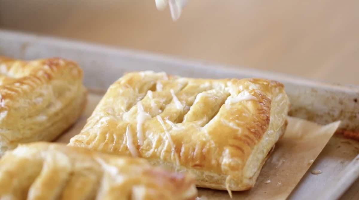 drizzling frosting on an apple cinnamon pastry
