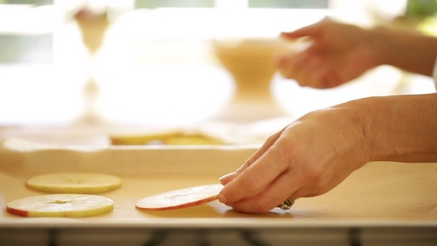 Placing apple slices on a baking sheet with parchment paper