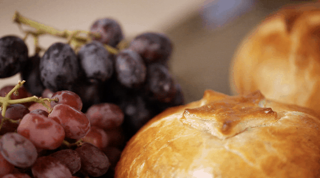 Baked brie in puff pastry with grapes in background