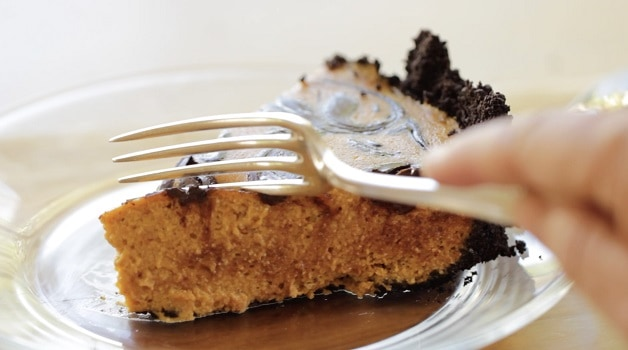 Fork cutting into slice of Chocolate Pumpkin Cheesecake