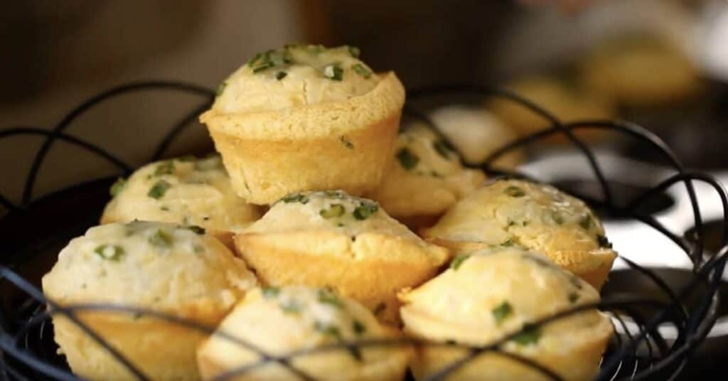 A close up of food, with BreaCornbread muffins topped with chives piled on a black wire cakestand