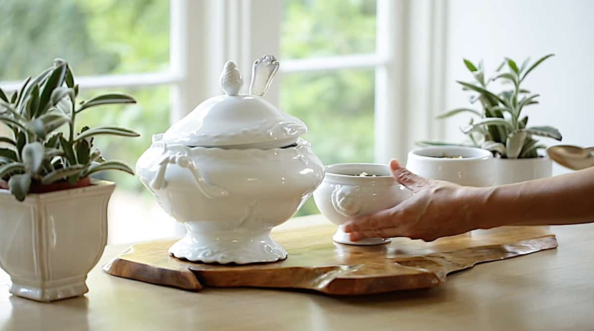 a person bring bowls of soup to a table set with a white French-style soup tureen