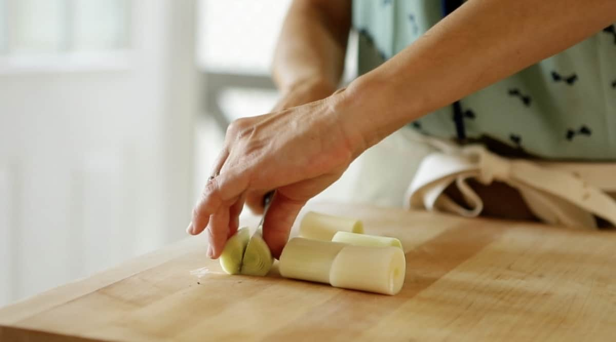 a person slicing leeks on a cutting board