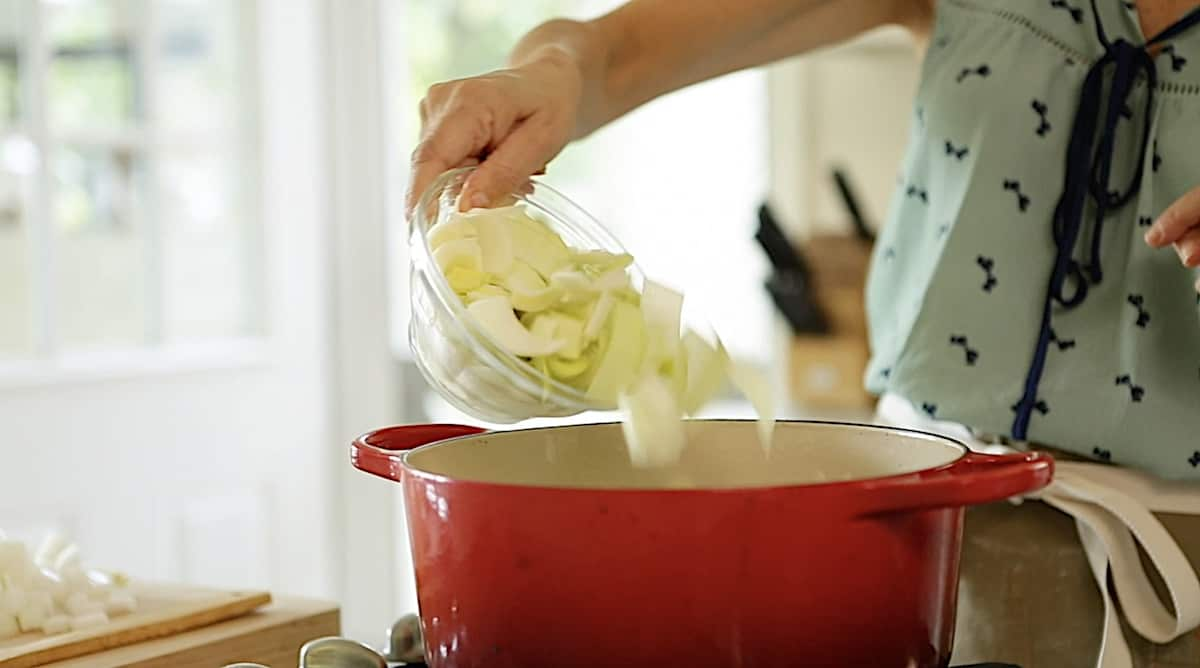 a person adding chopped leeks to a red Dutch oven