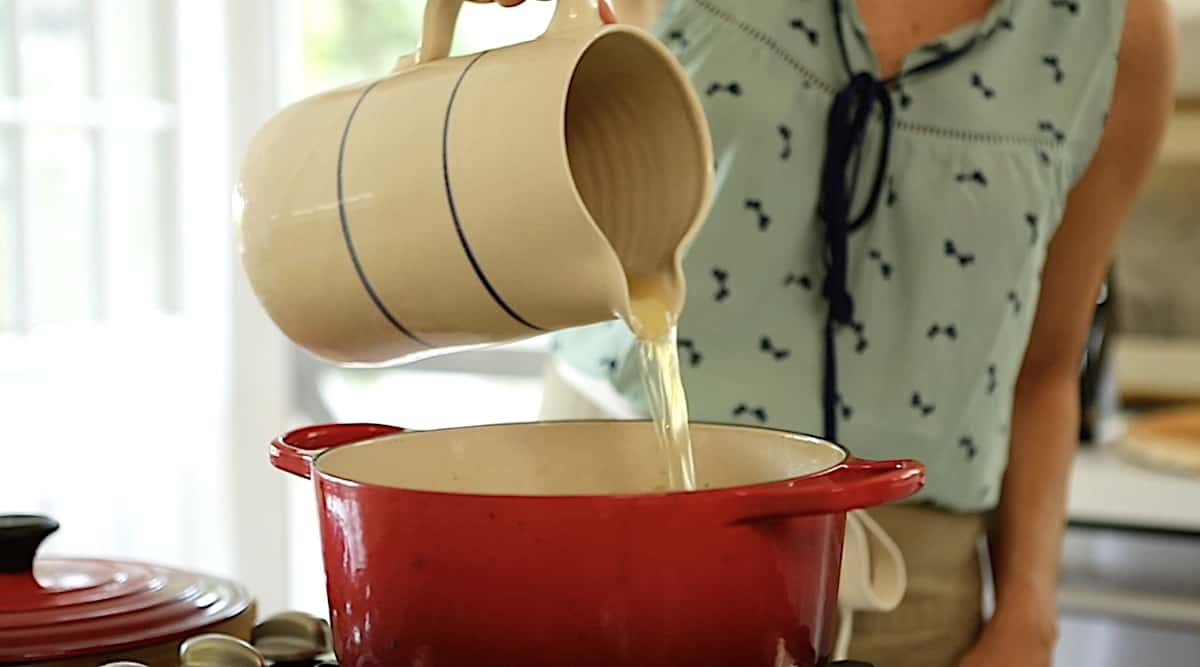 a person adding broth from a pitcher to a pot