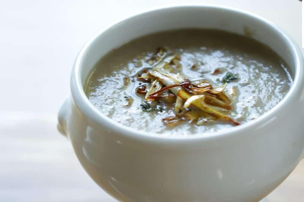 Cream of Mushroom Soup with Crispy Leek Garnish in a white soup bowl