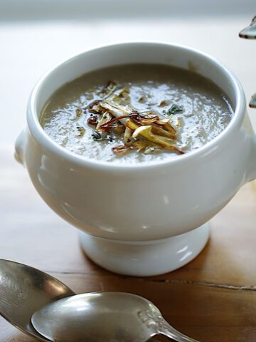 Cream of Mushroom Soup with Crispy Leeks and silver spoons