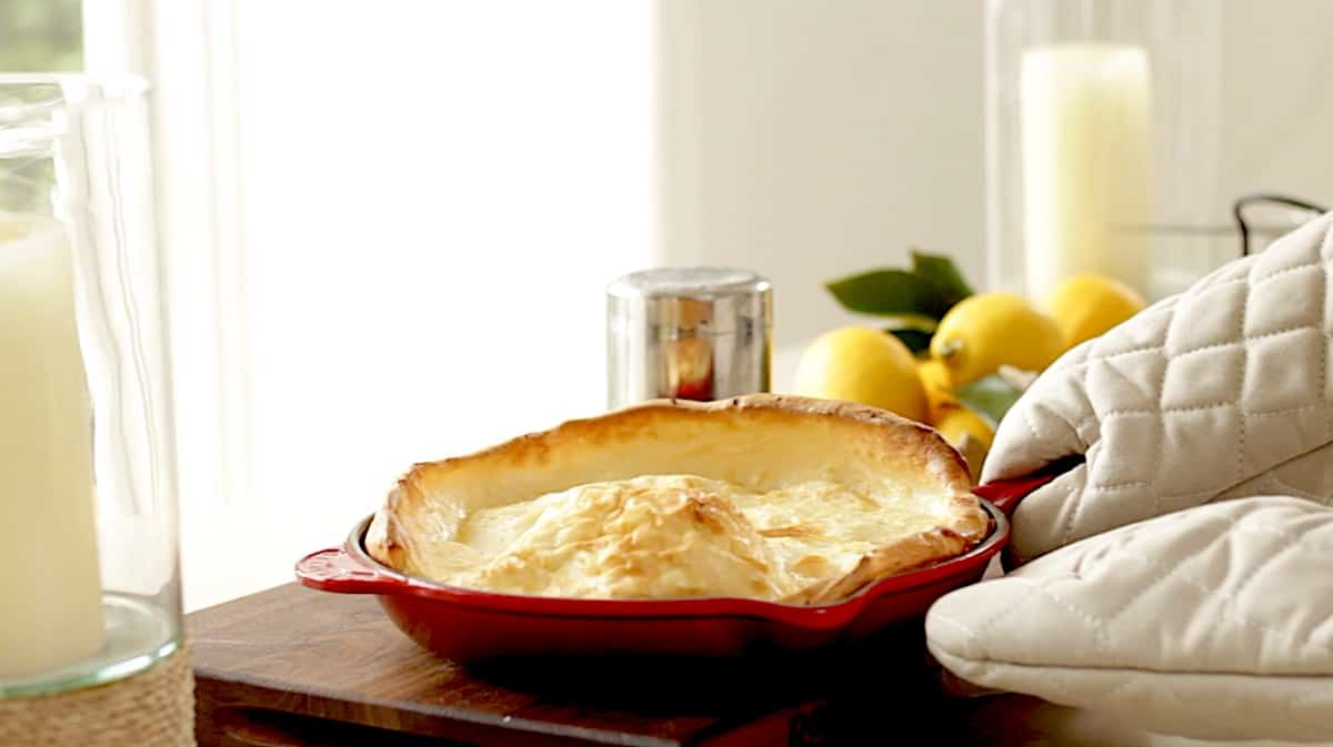 A person brining a Dutch Baby Pancake to the table