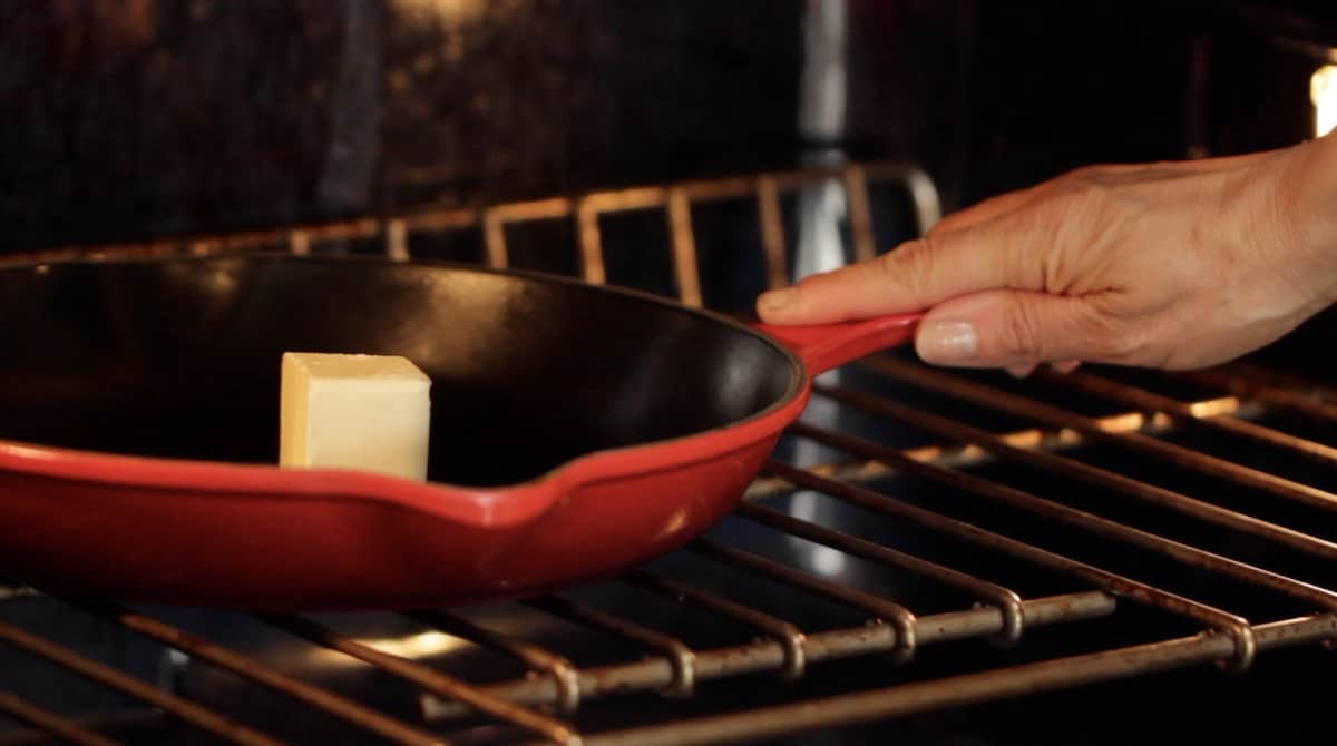 a person placing a red cast iron pan in the oven with butter