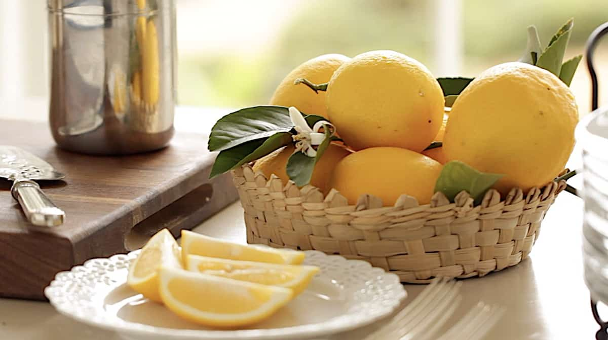 a basket of lemons and sliced lemons and powdered sugar canister on a table