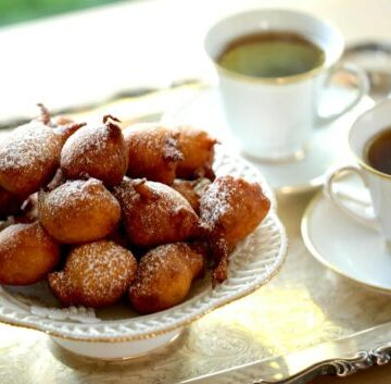 Apple Fritters piled on white cake stand served on a silver tray with coffee