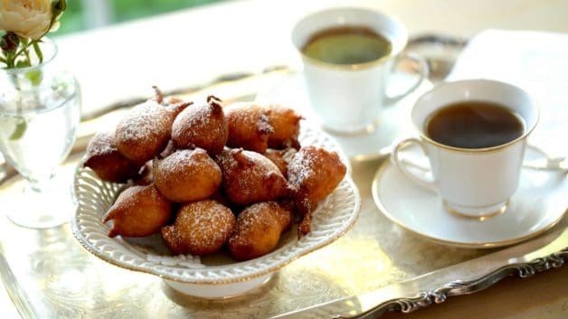 Easy Apple Fritter Recipe piled on white cake stand served on a silver tray with coffee
