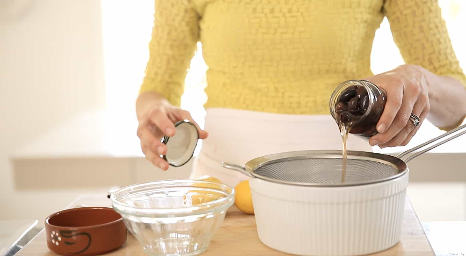 A person draining olives from a jar into a strainer