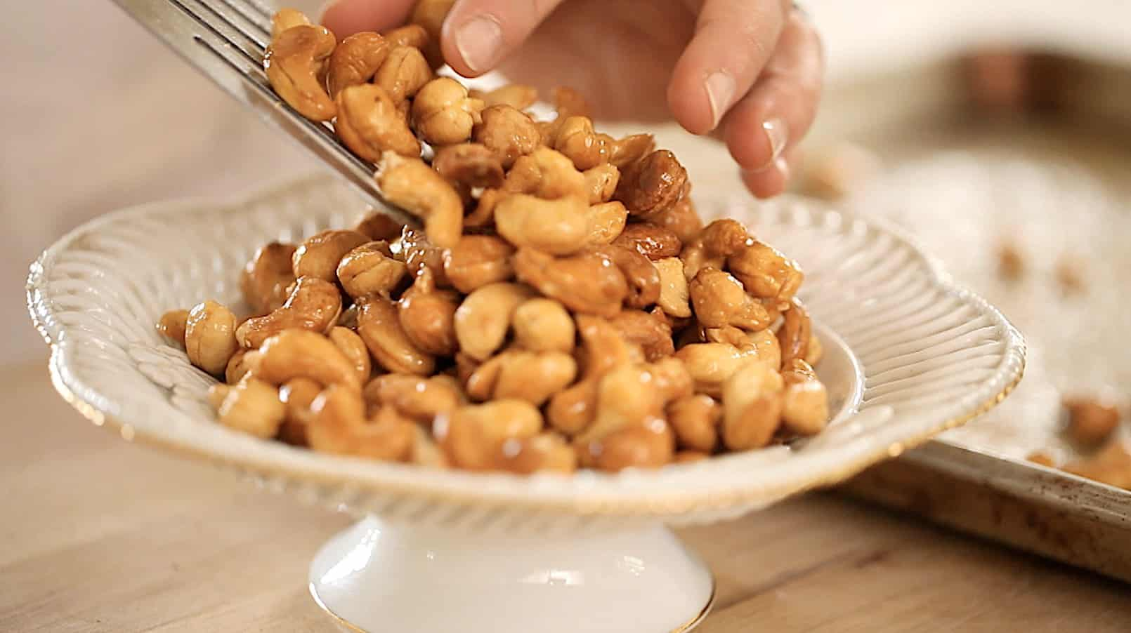 a person adding honey nuts to a bowl