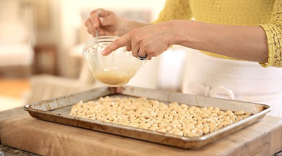 a sheet pan of cashews with a person about to add a honey glaze
