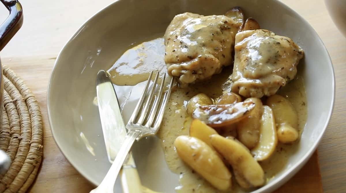 Braised Chicken Thighs on a Gray Bowl with potatoes and silverware