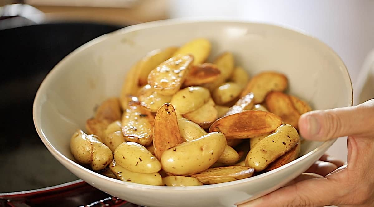 Transferring Caramelized potatoes from a pot to a bowl
