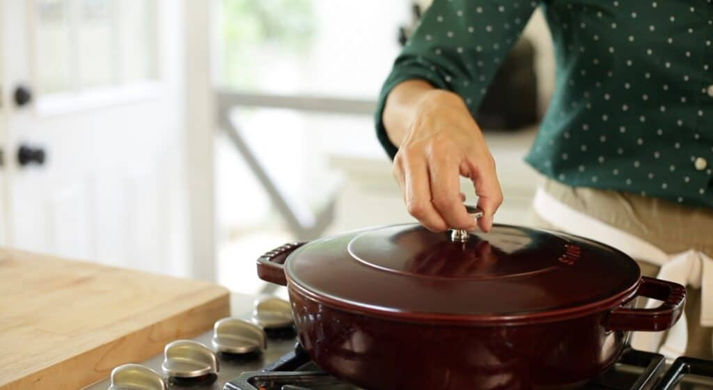 A person placing a lid on a maroon braiser