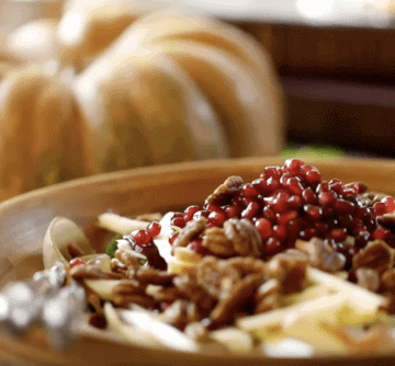 Fall Harvest Salad topped with pomegranate seeds in a large wooden bowl