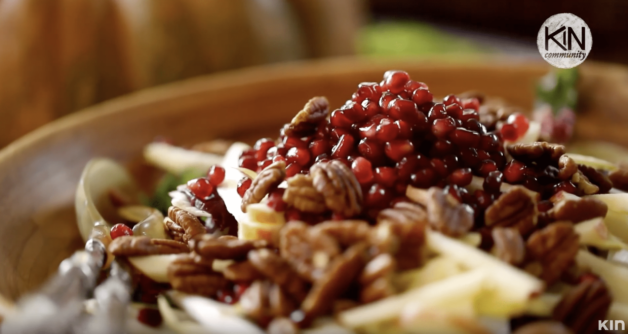 Salad with nuts, pomegranates and greens in a large wooden bowl