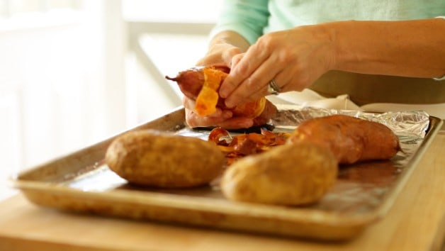 Peeling freshly baked sweet potatoes on a sheet pan