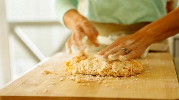 Shaping gnocchi dough on a floured cutting board
