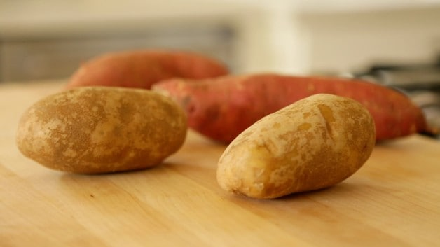 Sweet potatoes and russet potatoes on cutting board