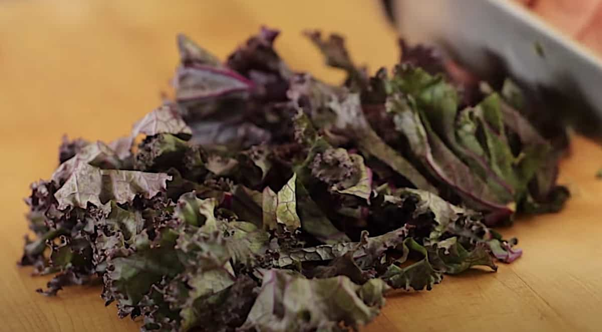 Red kale being chopped on a cutting board